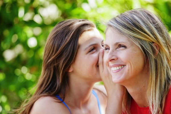 Teen whispering in the ear of her mother